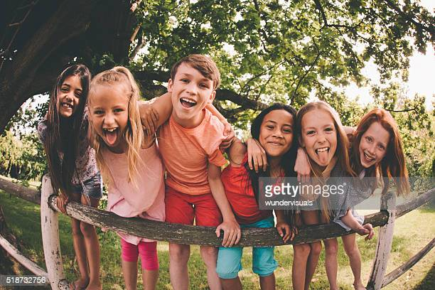 Row of children on a fence in a park laughing