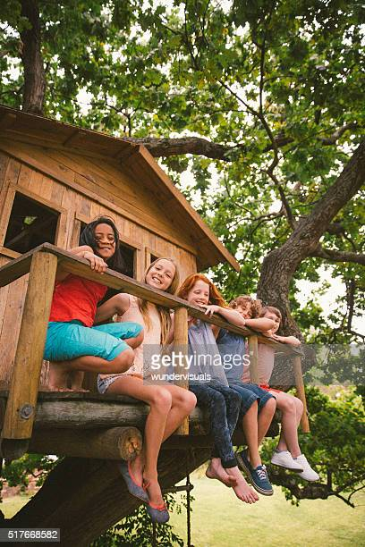 Row of children sitting on a wooden treehouse