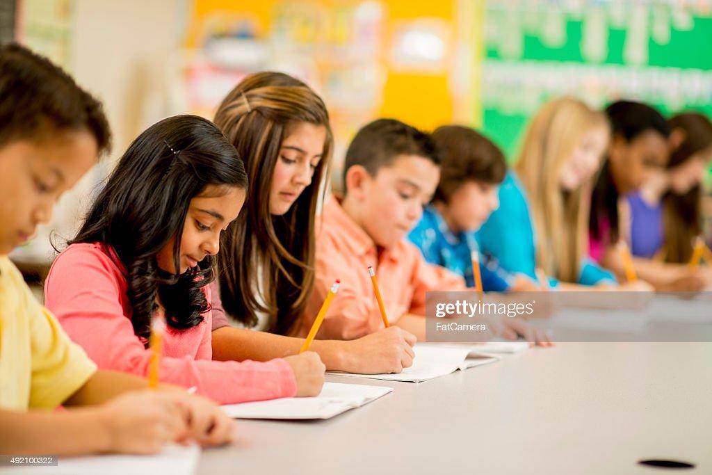 Reihe von Kindern, die auf Assignment : Stock-Foto