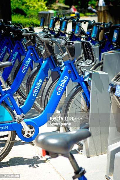 row of city bikes for rent at docking stations in new york - bicycle parking station stock photos and pictures