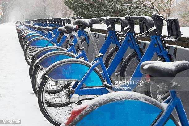 Row of city bikes in snow