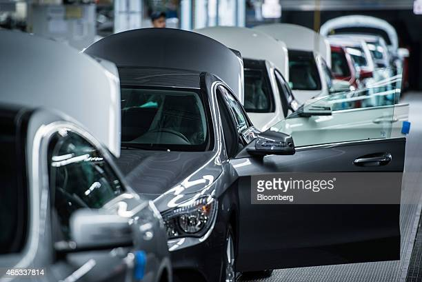 A row of CLAclass automobiles stand on the production line with their doors open at the MercedesBenz AG plant operated by Daimler AG in Kecskemet...
