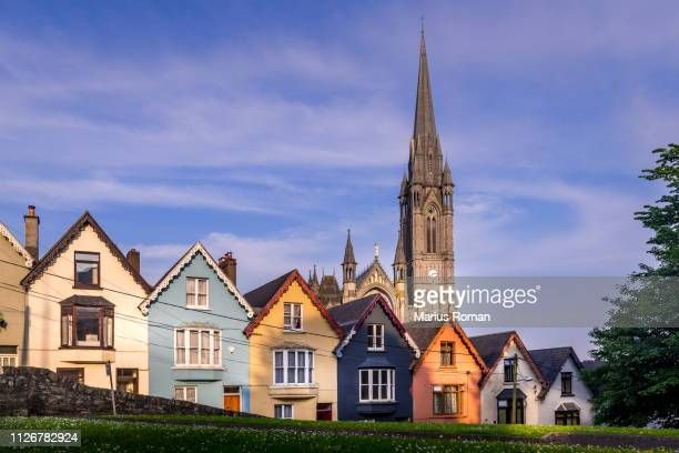 row of colorful houses with cathedral background in cobh, county cork, ireland. - county cork stock pictures, royalty-free photos & images