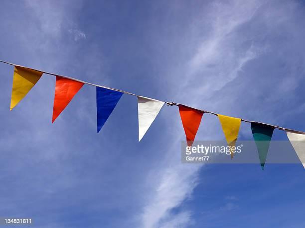 Row of coloured flags against the sky