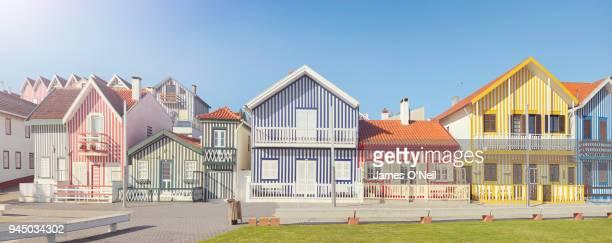 row of colourful beach houses in costa nova, portugal - uferpromenade stock-fotos und bilder