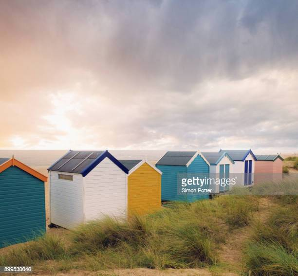 row of colourful beach huts and storm clouds over sea, southwold, suffolk, england - suffolk england stock photos and pictures