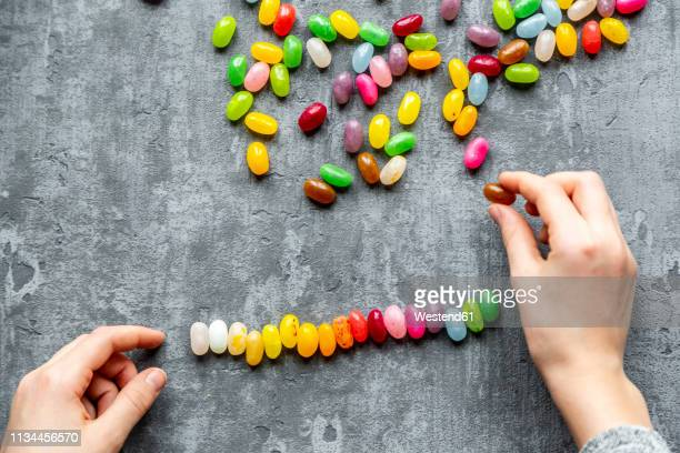 row of colourful sweet jellybeans on gray background - rangschikken stockfoto's en -beelden