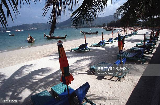 A row of deckchairs and colourful parasols on a fine white sand beach in Southern Thailand The country's beach resorts are a popular destination for...