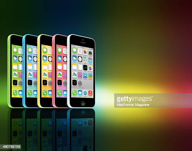 A row of different coloured Apple iPhone 5C smartphones photographed on a rainbow background taken on September 20 2013