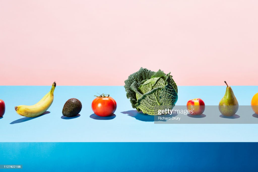 A row of different fruits and vegetables on a table top : Stock Photo