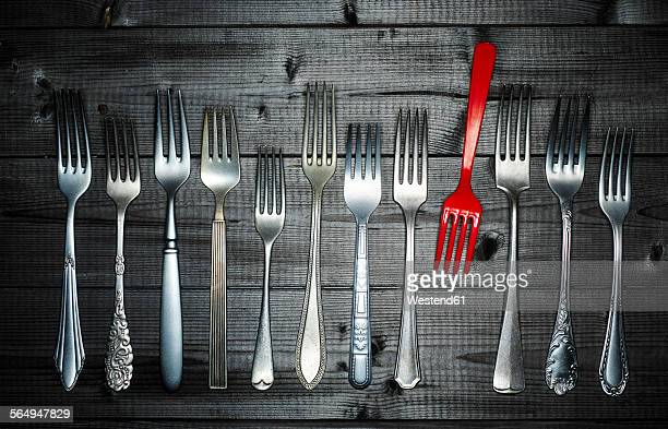 Row of different silver forks and a red plastic fork on wood