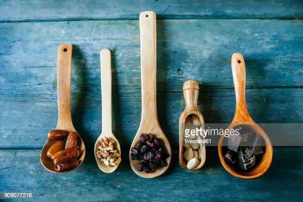 Row of different wooden spoons with dates, walnuts, currants, almonds and dark chocolate
