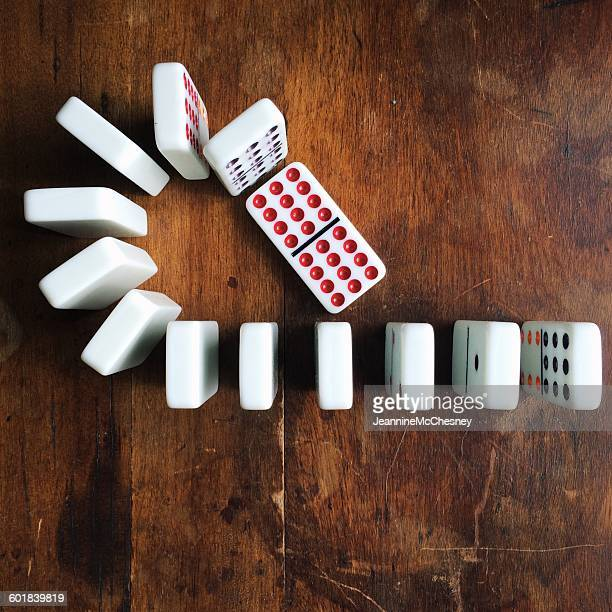 Row of dominos on a wooden table