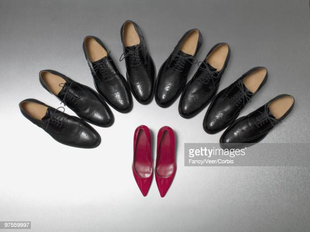 row of dress shoes surround high heels - stiletto stock pictures, royalty-free photos & images