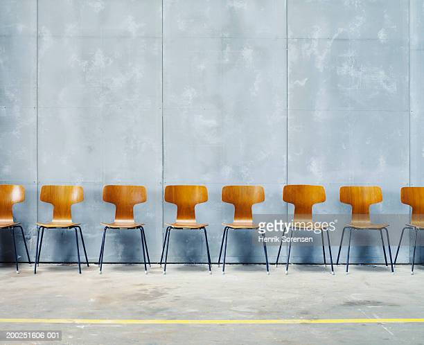 row of empty chairs against wall - 椅子 ストックフォトと画像