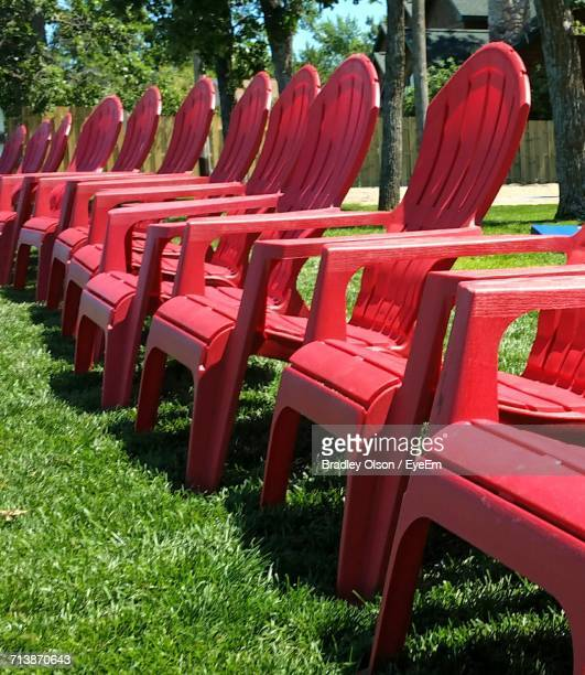 Row Of Empty Red Adirondack Chairs On Grass
