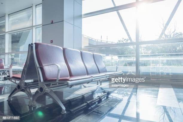 row of empty seats in airport lobby - hospital building stock photos and pictures