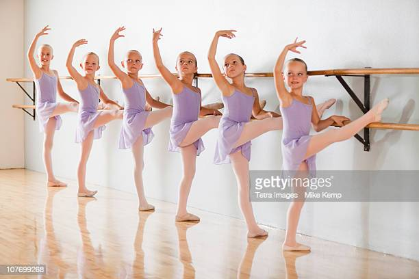 Row of female ballet dancers (6-7,8-9) in dance studio