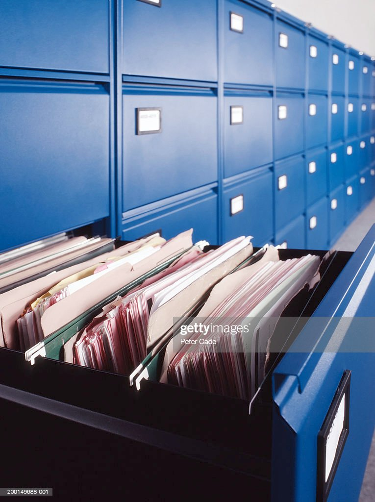 Row of filing cabinets with one open drawer : Stock Photo