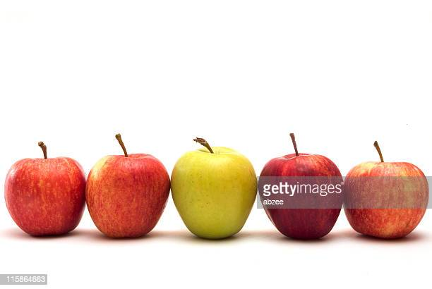 Row of five apples with different colors on a white surface