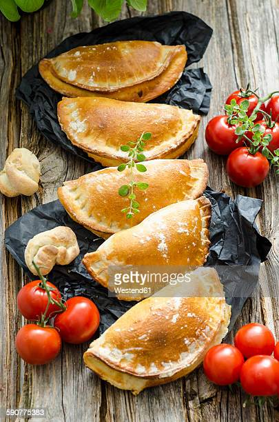 Row of five Calzone stuffed with tomatoes and sage
