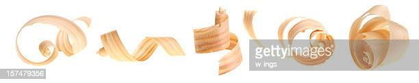 Row of five curled wood shavings on a white background