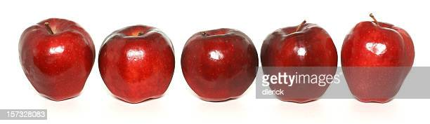 row of five red apples on white
