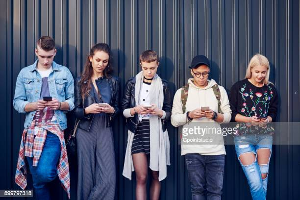 row of five young adult friends leaning against black wall looking at smartphones - geração z imagens e fotografias de stock