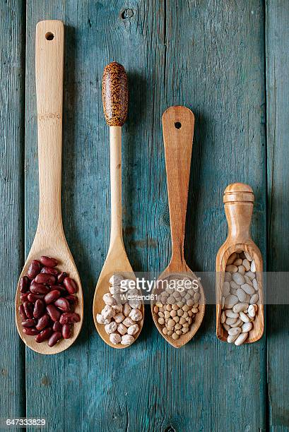 Row of four different wooden spoons with various pulses