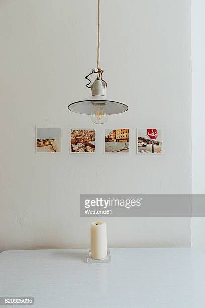 Row of four polaroids on a wall, old ceiling light and a candle on table top