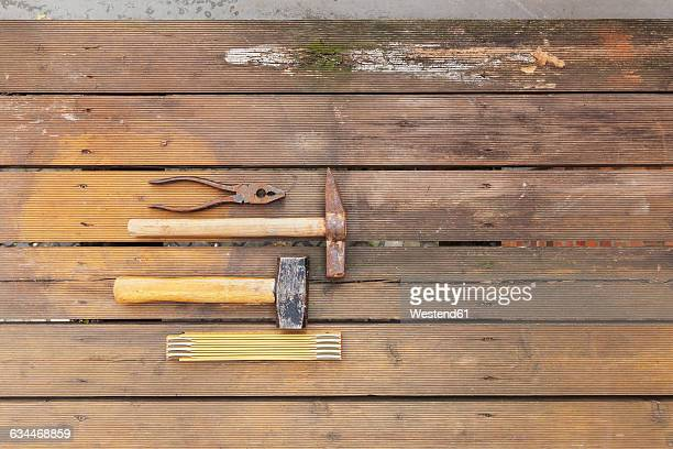 Row of four tools lying on rotten balcony floarboards