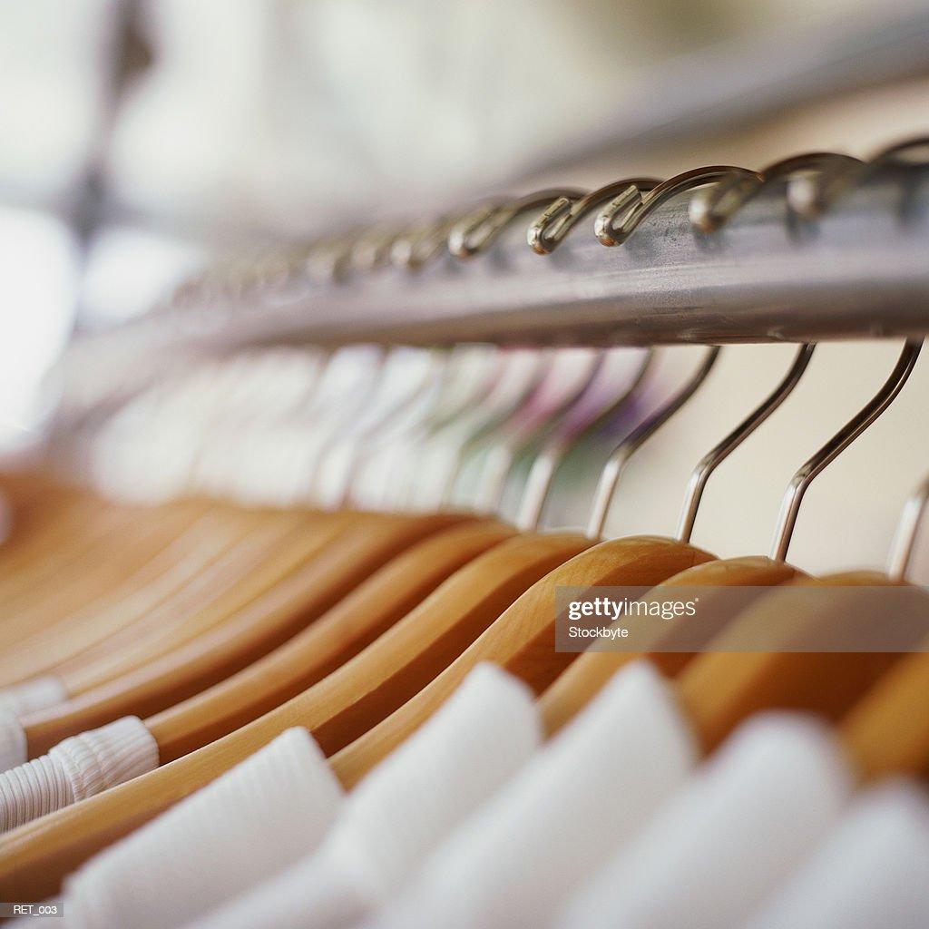 Row of garments on wooden hangers : Stock Photo