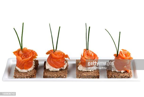 A row of garnished salmon canapes on a white platter