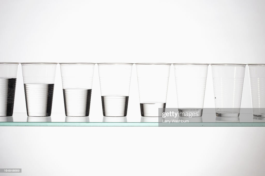 A row of glasses with varying amounts of water descending from full to empty : Stock Photo