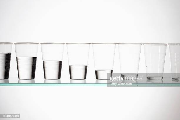 A row of glasses with varying amounts of water descending from full to empty