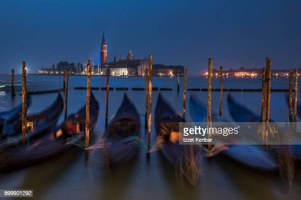 Row of gondolas blurred by the motion of the waves at San Marco square quay, Venice Veneto, Italy