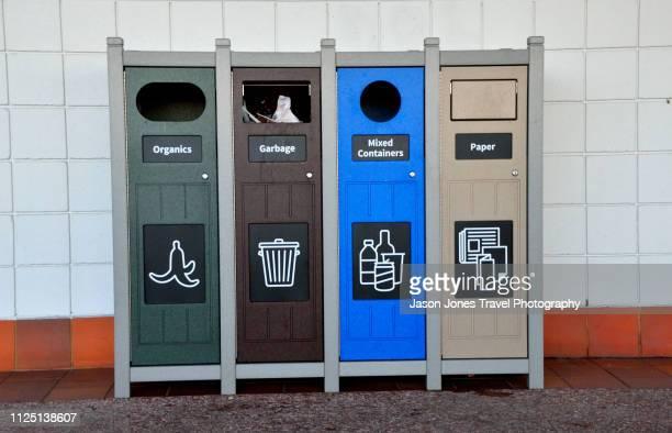 row of green recycling bins - ゴミ容器 ストックフォトと画像