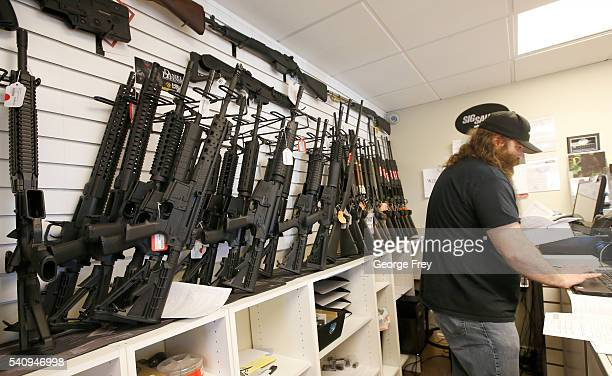A row of guns many that are AR15's line the wall as owner of Ready Gunman Willy Ludlow works on paperwork on June 17 2016 in Springville Utah...