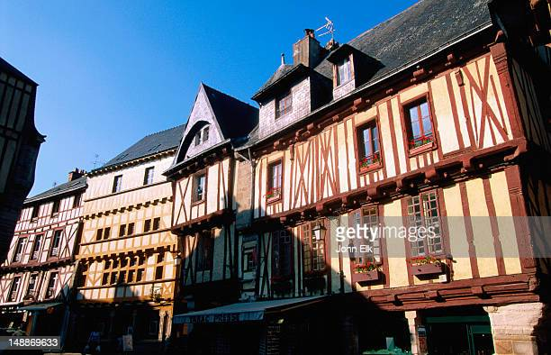 a row of half-timbered houses facing a street in shadow - ヴァンヌ ストックフォトと画像