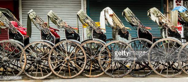 row of hand pulled rickshaw in kolkata - striker stock pictures, royalty-free photos & images