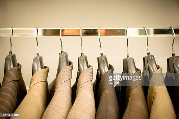 Zeile der Anzüge im Schrank hängen