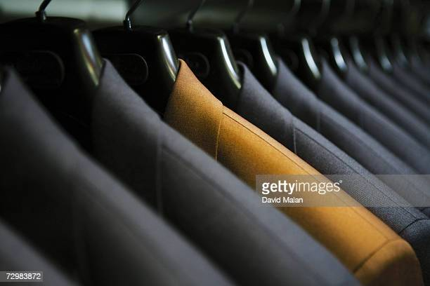row of hanging suits in wardrobe - individualidad fotografías e imágenes de stock