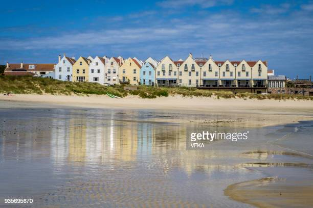 row of houses and a hotel, reflected in the water at braye beach, alderney, guernsey, channel islands - isola di guernsey foto e immagini stock