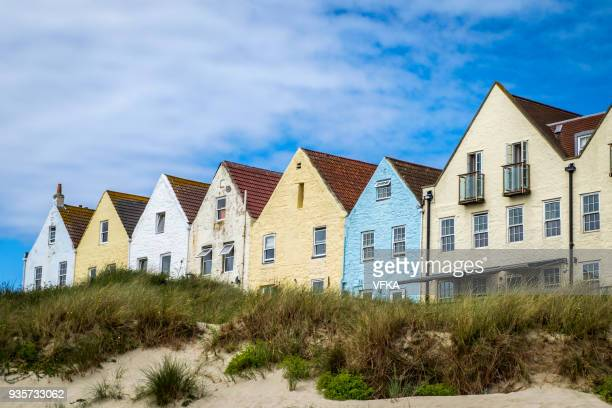 row of houses and at braye beach, alderney, guernsey, channel islands - isola di guernsey foto e immagini stock