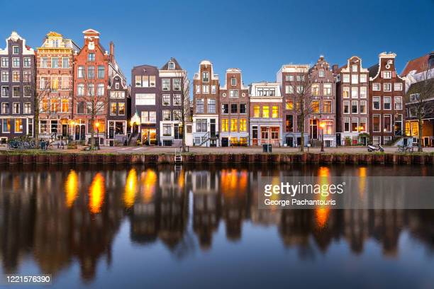 row of houses in the canals of amsterdam - amsterdam stock pictures, royalty-free photos & images