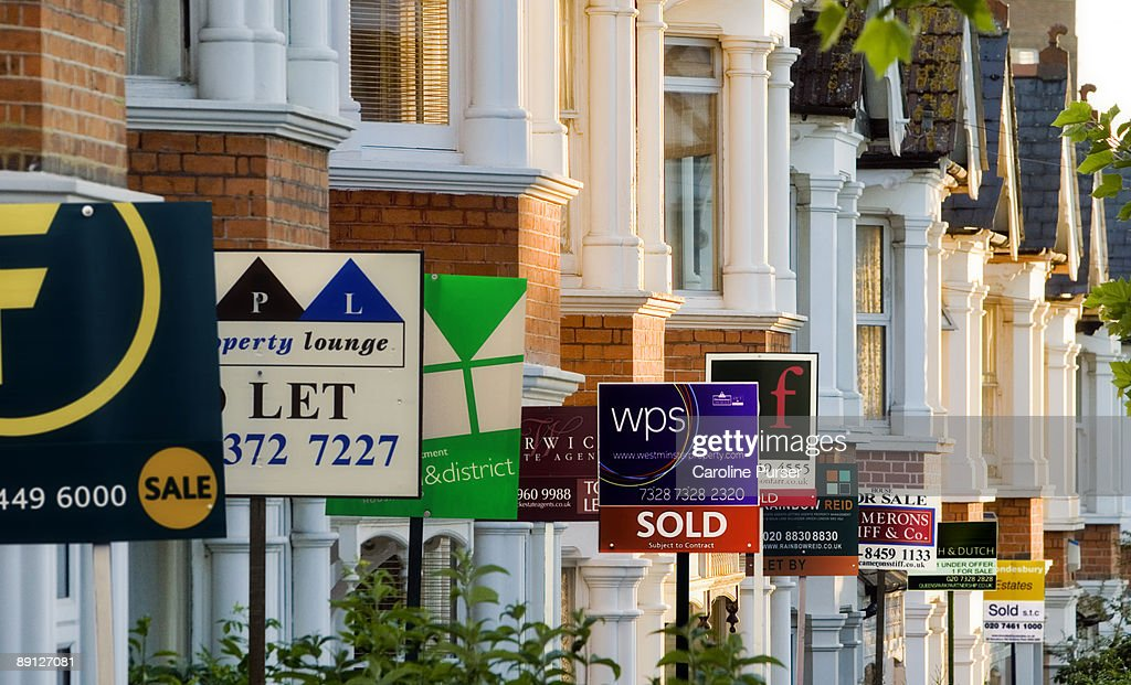 Row of houses with for sale signs in front of them : Stock Photo