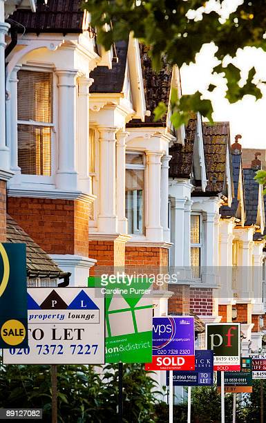 row of houses with for sale signs in front of them - estate agent sign stock pictures, royalty-free photos & images