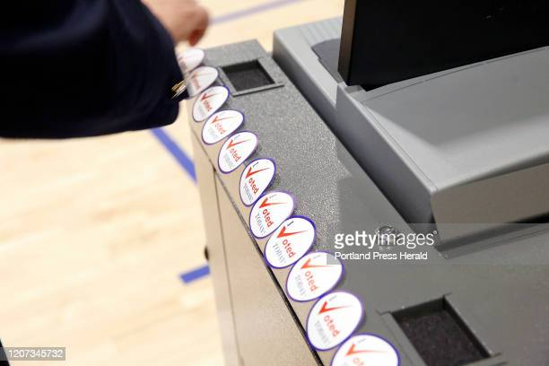 """Row of """"I voted today"""" stickers stand at the ready on a ballot box on Super Tuesday at Falmouth High School."""