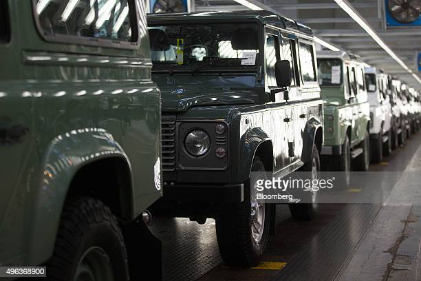 A row of Land Rover Defender automobiles sit on the inspection line at Tata Motors Ltd's Jaguar Land Rover vehicle manufacturing plant in Solihull UK...