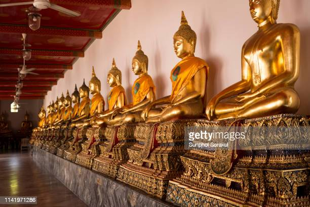 row of large bronze buddha statues along the inner cloister of wat pho - wat pho stock pictures, royalty-free photos & images